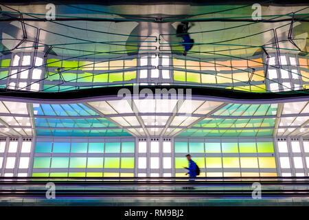 Air passenger, person walking, neon lights art installation, Michael Hayden, pedestrian tunnel, Chicago O'Hare International Airport Terminal, USA - Stock Image