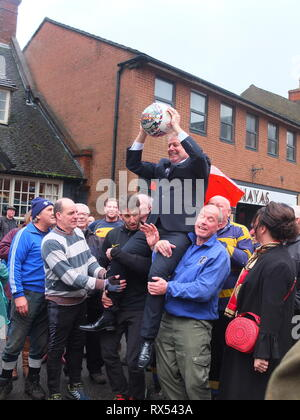 Ashbourne Shrovetide Football 2019. Local firefighter Paul Holmes is paraded with the ball he will turn up to begin the Ash Wednesday Game. - Stock Image
