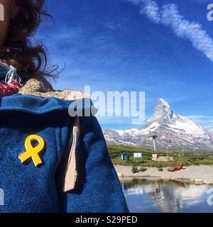 Catalan tourist with a yellow ribbon pinned in her blue jacked in support of jailed pro-independence Catalan politicians. View of Matterhorn, Zermatt, Wallis or Valais, Switzerland. - Stock Image
