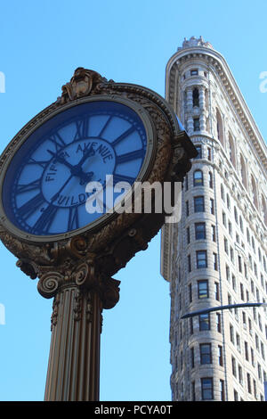Iconic cast-iron Fifth Avenue Building street clock seen against Flatiron Building, Flatiron District, Manhattan on JULY 5th, 2017 in New York, USA. ( - Stock Image