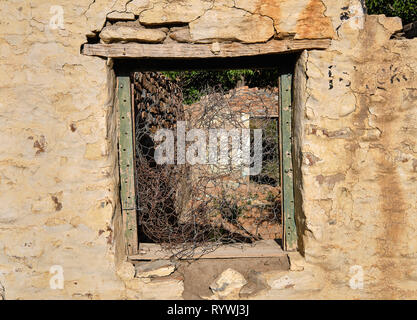 Central empty green window frame on rocky wall of abandoned house.  Through frame see barbed wires and rest of structure in ruin - Stock Image