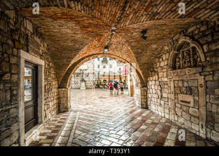 The Square of the Arms opens out in front as tourists enter the gated, walled medieval fortress town of Kotor, Montenegro through it's tunnel entrance - Stock Image