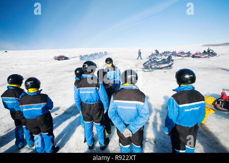 Tourists on a skidoo trip on the Langjokull ice sheet, which is retreating rapidly due to climate change. Scientists reckon that all of Iceland's glaciers will have disappeared in 100 years. - Stock Image
