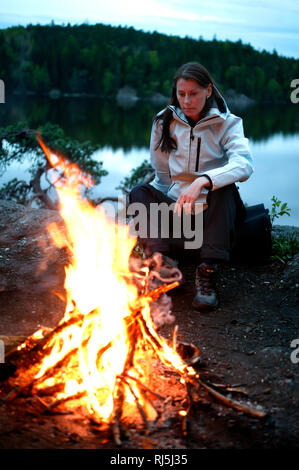 Woman sitting by a fire - Stock Image
