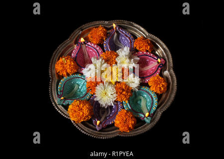 A plate used for traditional hindu rituals with lamps and flowers during Diwali festival in India. - Stock Image
