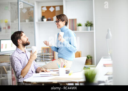 Conversation of two young contemporary brokers with drinks during coffee break in office - Stock Image