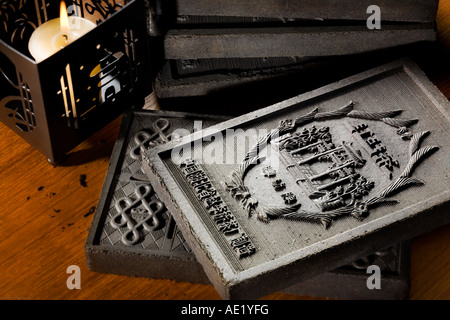 Embossed tea bricks on a table near a lit candle. - Stock Image