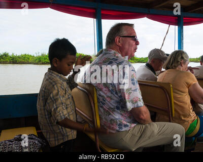 Helmsman's son giving tourist a back massage while cruising along Tonle Sap Lake Siem Reap Cambodia Asia - Stock Image