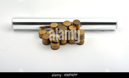 Aluminium foil with coins isolated on white background - Stock Image