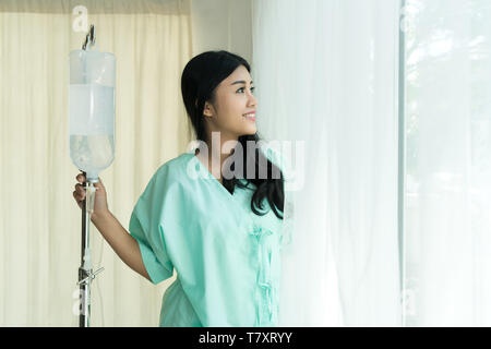 Asian patients woman looking outside the window, Patients is glad recovered from the illness. - Stock Image