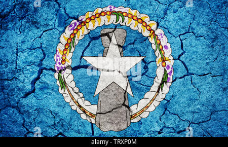 Flag of the Commonwealth of the Northern Mariana Islands on dry earth ground texture background - Stock Image