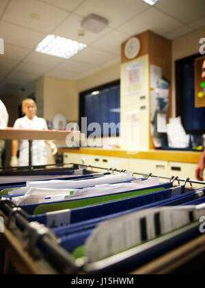 Patient notes with medical staff walking in background  on busy ward in large general hospital - Stock Image