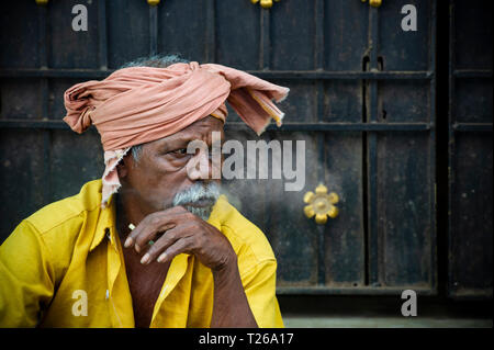 A wise looking man with a turban style hat smokes a cigarette and exhales the smoke - Stock Image