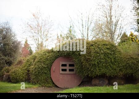A tiny 'hobbit house' with round door at the Oregon Garden in Silverton, Oregon, USA. - Stock Image