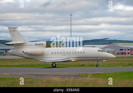 Preparing to depart for Dubai this Falcon DX powers up on the runway at Inverness Dalcross Airport in the Scottish - Stock Image