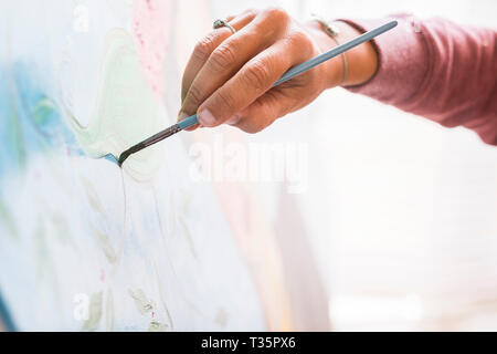 Closeup of woman hand painting an art wallpaper with old style - creativity and artist at work for hobby or job - colors and background concept - Stock Image