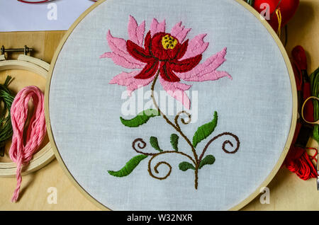 Hoops with embroidered stylized flower of red and pink petals on swirling branches with leaves on white cotton fabric on black background - Stock Image