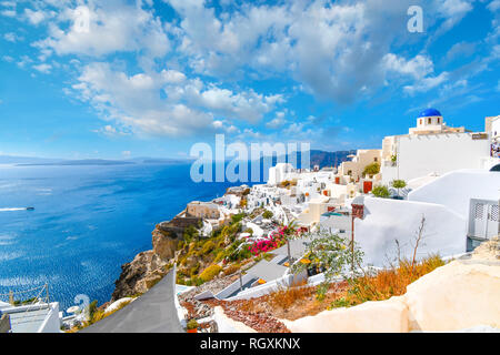 Oia, Santorini, Greece. Whitewashed houses and blue dome church highlight the island as tourists enjoy a resort terrace summer view of the Aegean Sea - Stock Image