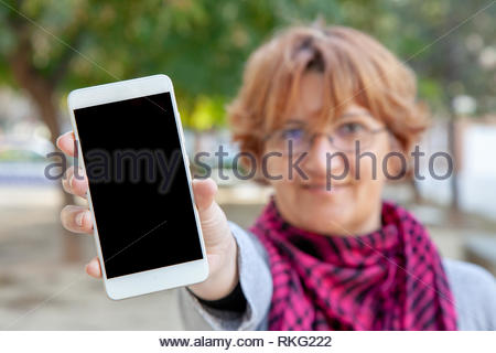 A woman holds a white mobile phone with an empty screen in an outdoor location. - Stock Image