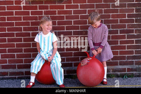 Girls playing on bouncy ball with handles - Stock Image
