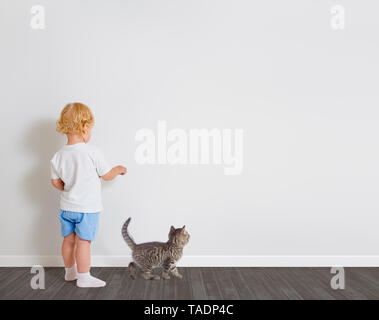 Baby boy drawing on wallpaper standing back to camera with little cat - Stock Image