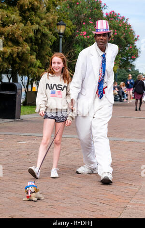 Uncle Louie, a street performer, busker, busking, posing as a living statue with a young tourist by the Mississipi River, New Orleans French Quarter. - Stock Image