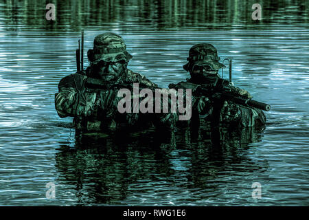 Pair of soldiers in action during a river raid in the jungle at night. - Stock Image