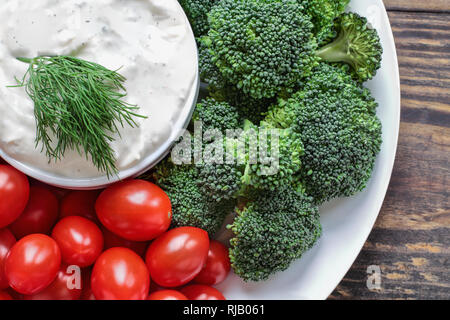 Homemade buttermilk ranch salad dressing with dill served with fresh cherry tomatoes and broccoli over a rustic wooden background. Image shot above fr - Stock Image