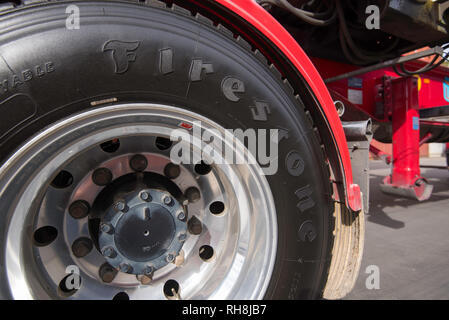 A close up image of a shiny black painted tyre, tire of a large red prime mover truck parked and stationary - Stock Image
