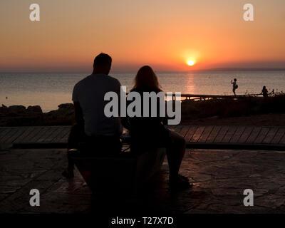 Sunset in Ayia Napa Cyprus , a colourful sunn setting in the Mediterranean sea with silhouetted tourists - Stock Image