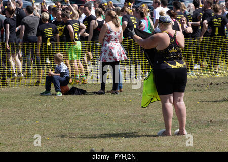 Large lady at the start of an obstacle course mud run - Stock Image