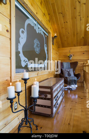 Candelabra with lit candles, stained glass window with Norwegian motifs, metal and leather chest, brown leather arm chair on mezzanine in log cabin - Stock Image