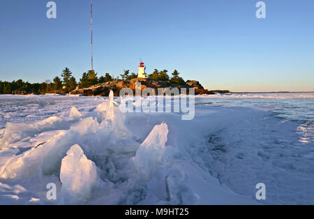 Georgian Bay Killarney Lighthouse, built in 1850s, with frozen lake and dramatic ice formations at dusk in early spring - Stock Image