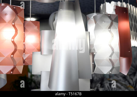 Modern design plastic chandeliers of matte white and light red colors with glowing lamps, viewed in close-up - Stock Image