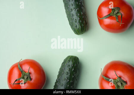 Ripe raw organic tomatoes cucumbers on light lettuce green background. Balanced diet vegan superfoods healthy lifestyle vitamins concept. Creative pos - Stock Image