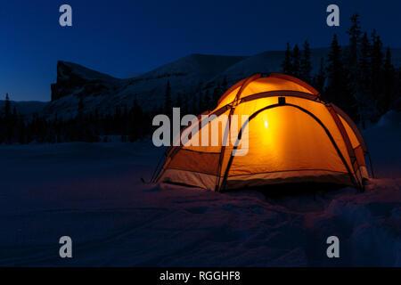 Camping in winter season at night, lantern shining in the tent, Mount Skerfe and Sarek national park in background, Jokkmokk county, Sarek national pa - Stock Image