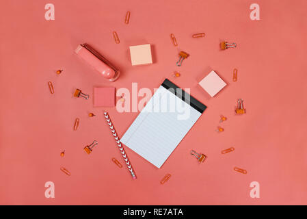 Blank white note pad paper, pencil, stapler, thumb tacks, paper clips, and adhesive paper over coral color background with free space for text. Image  - Stock Image