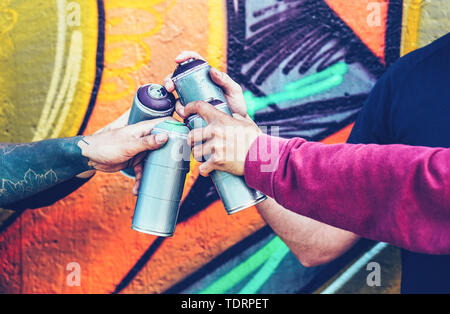 Group of graffiti artists stacking hands while holding spray color cans against mural background - Young painter at work - Stock Image
