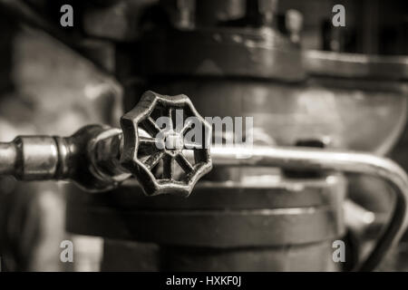 Close up of a stopcock on an old industrial machine in sepia. - Stock Image