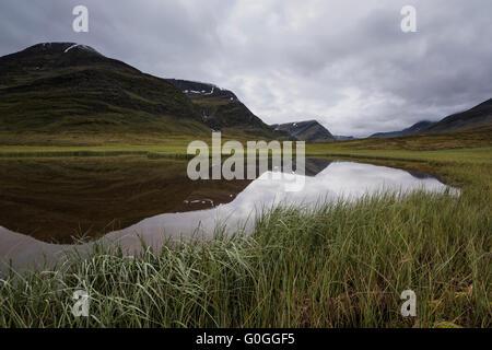 Reflection of mountain landscape of Tjäktjavagge valley in small pond near Sälka hut; Kungsleden trail; - Stock Image