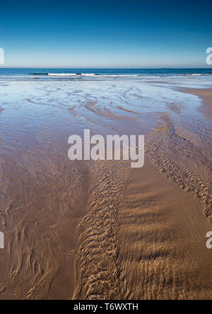 A tranquil scene of the sandy beach at Bamburgh, Northumberland, England UK with a stream flowing towards the sea. - Stock Image