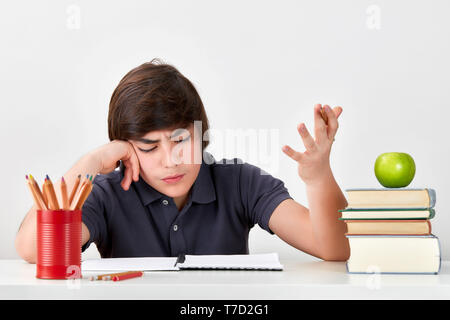 Secondary school boy student with ADHD is feeling confused and angry while doing his homework - Stock Image