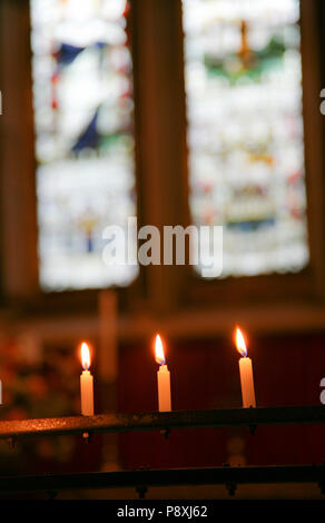 Candles burning as a remembrance ahead of a stained glass window in a small church in Dublin, Ireland, Europe. - Stock Image