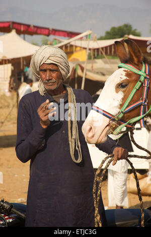 Rajasthani man with horse at the Pushkar fair. Rajasthan, India - Stock Image