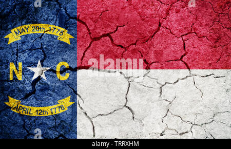 Flag of the state of North Carolina on dry earth ground texture background - Stock Image