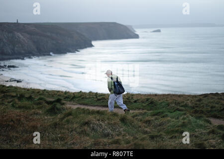 A man walking a coastal path in Cornwall during the winter. - Stock Image