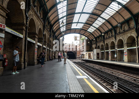 Passengers wait for a train at Notting Hill Gate London Undergorund Station. - Stock Image