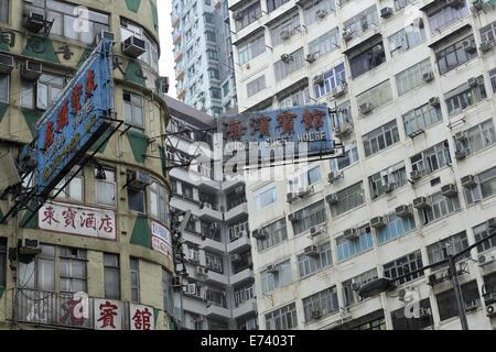 Signs advertising accommodation, amongst buildings of apartments and flats. Kowloon, Hong Kong, China - Stock Image