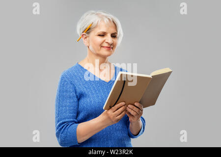 senior woman with pencil and diary or notebook - Stock Image