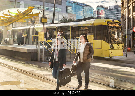 2 November 2018: Manchester, UK - Young couple smiling, with Debenhams shopping bags, in Exchange Square, with a Metrolink tram behind. Lots of flare. - Stock Image